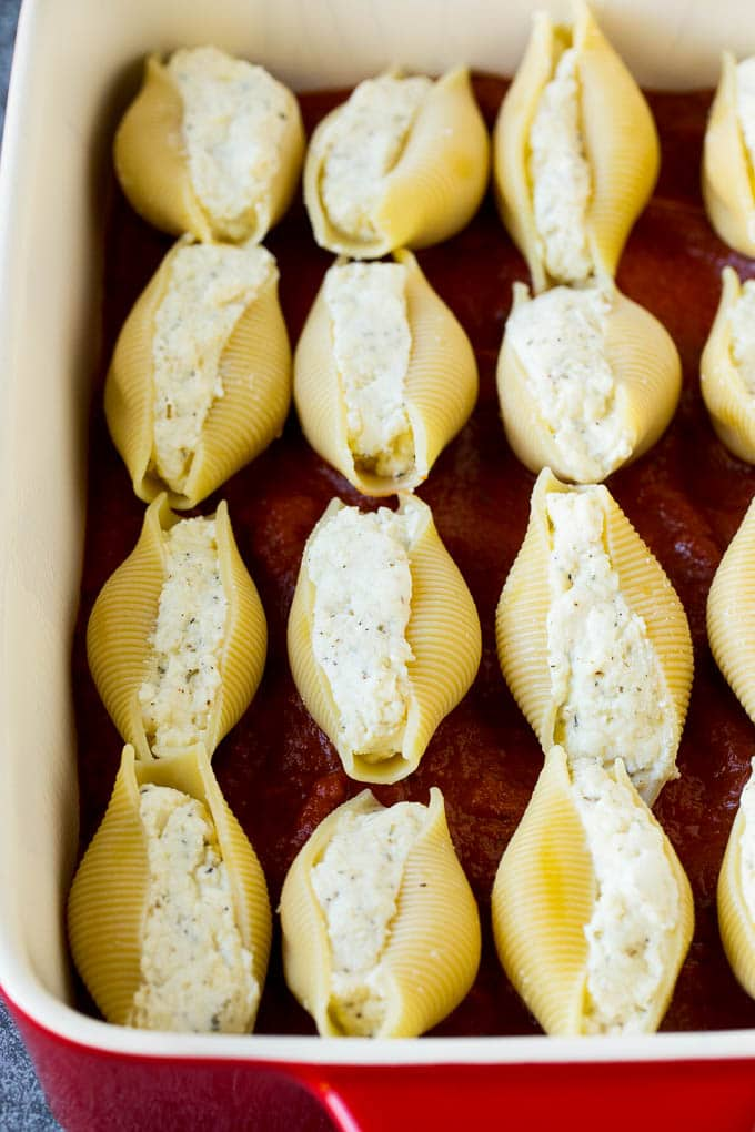 Pasta shells filled with cheese on a bed of tomato sauce.