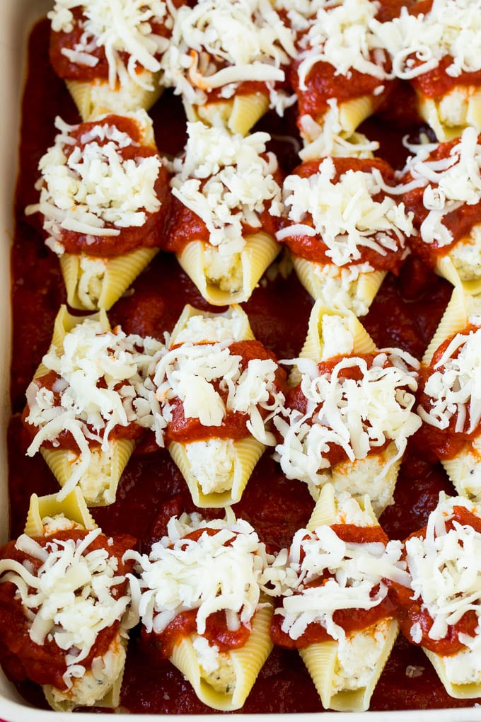 Filled pasta shells topped with marinara sauce and shredded cheese.