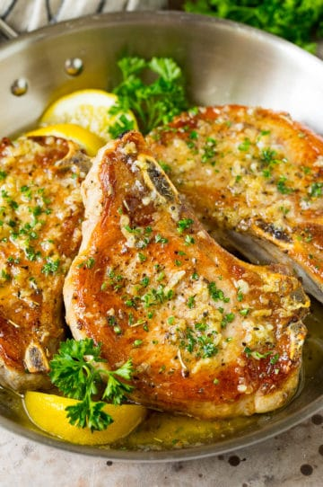 Baked pork chops in garlic butter, garnished with parsley and lemon.