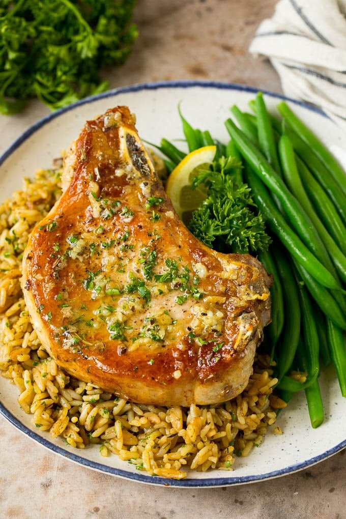 A baked pork chop served over rice with a side of green beans.