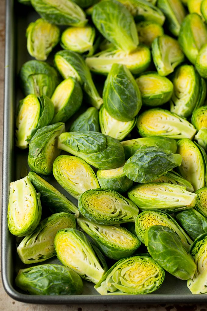 Halved sprouts on a sheet pan.