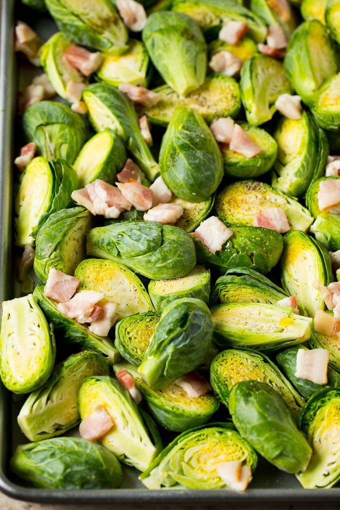 Brussels sprout halves and chopped bacon on a sheet pan.
