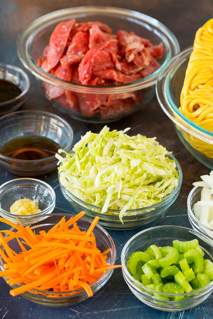 Bowls of ingredients including steak, carrots, celery, cabbage and noodles.