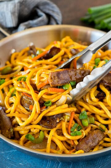 Tongs serving up a portion of beef lo mein.