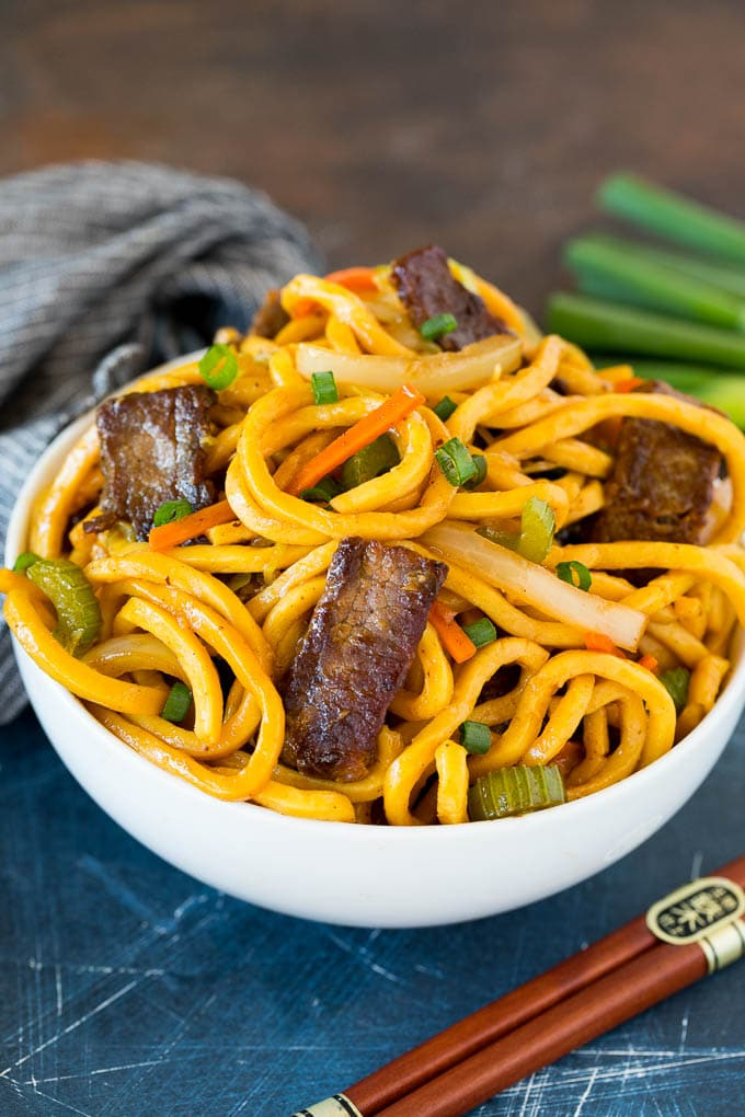 A bowl of beef lo mein topped with green onions.