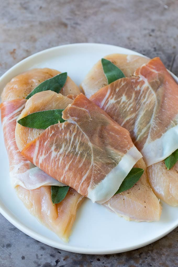 Raw chicken topped with fresh sage leaves and prosciutto.