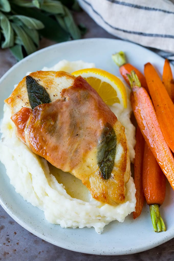 Chicken saltimbocca served over mashed potatoes with carrots on the side.