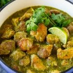 A pot of chile verde topped with cilantro and lime wedges.