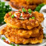 A stack of corn fritters topped with bacon, sour cream and green onions.