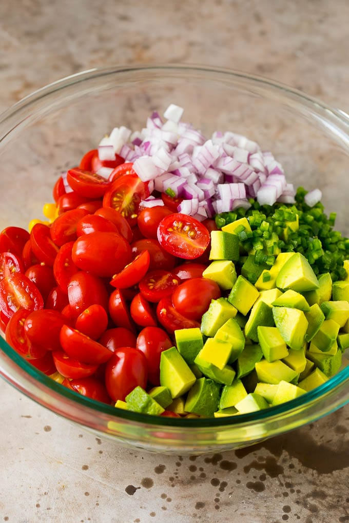 Corn, tomatoes, avocado, jalapeno and red onion in a bowl.