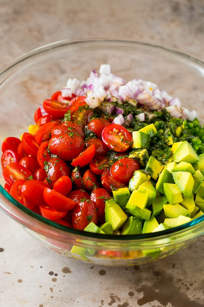 Dressing poured over tomatoes, corn and avocado in a salad bowl.