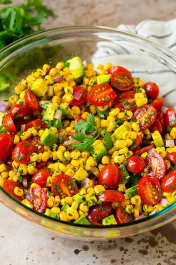 A bowl of corn salad with avocado and tomato, all tossed in a lime dressing.