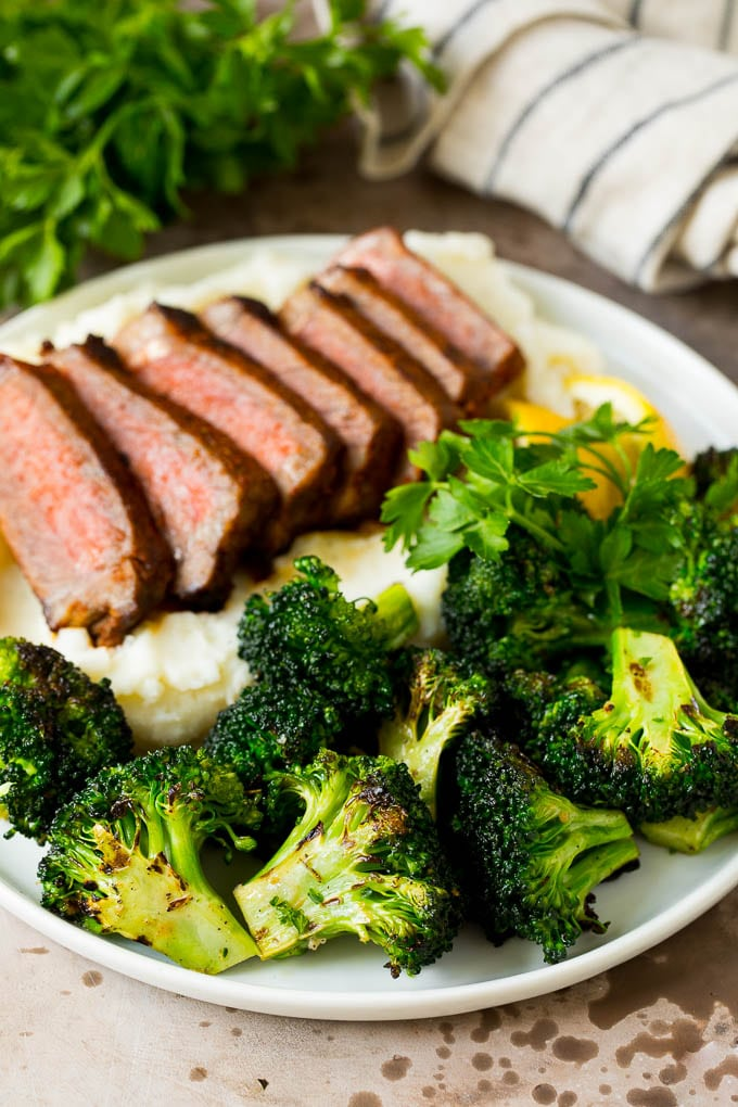 Grilled broccoli on a plate with steak and mashed potatoes.