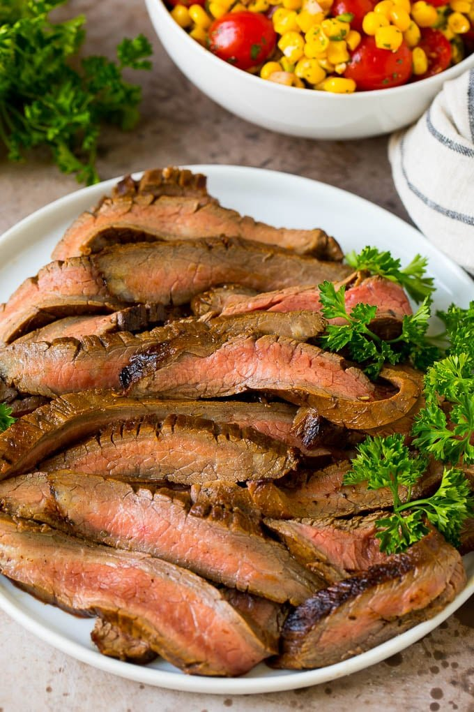 Sliced grilled flank steak garnished with fresh parsley.