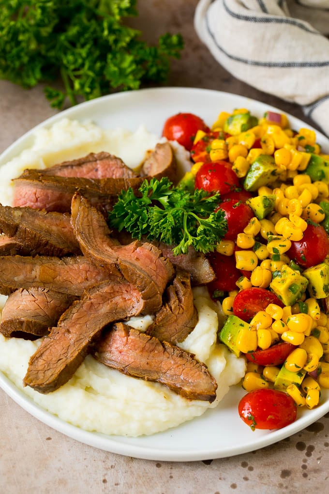 A plate of grilled flank steak served with mashed potatoes and corn salad.