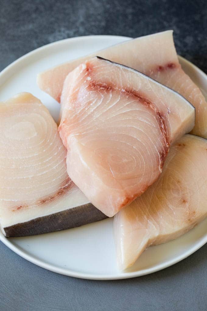 Raw fish fillets on a plate.
