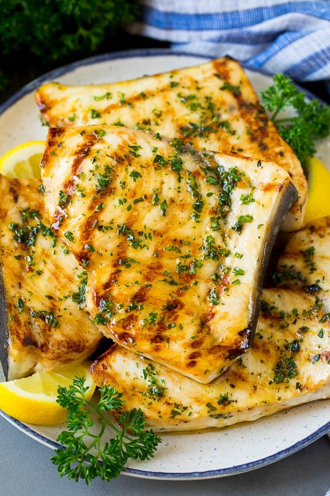 A plate of grilled swordfish steaks topped with herbs.
