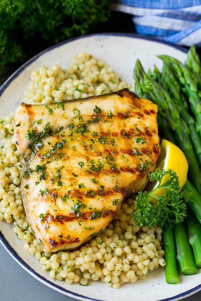 Grilled swordfish served with couscous and asparagus.