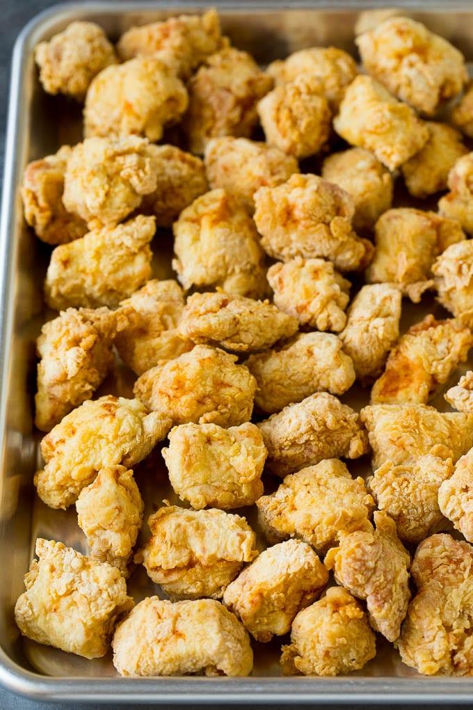 Deep fried chicken pieces on a sheet pan.