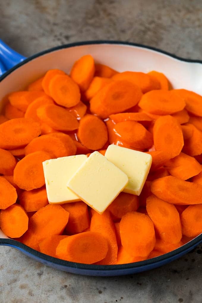 Cooked carrots, butter and honey in a pan.
