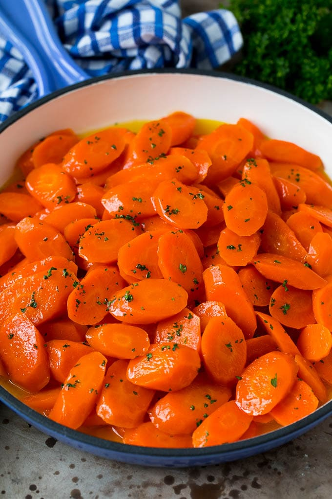Honey glazed carrots in a blue pan, topped with parsley.
