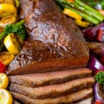 Smoked tri tip sliced and served on a pan with grilled vegetables.