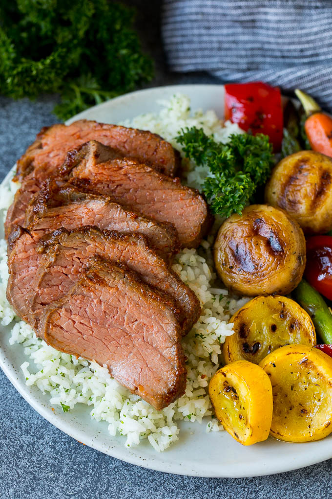 Slices of smoked tri tip served with rice and vegetables.