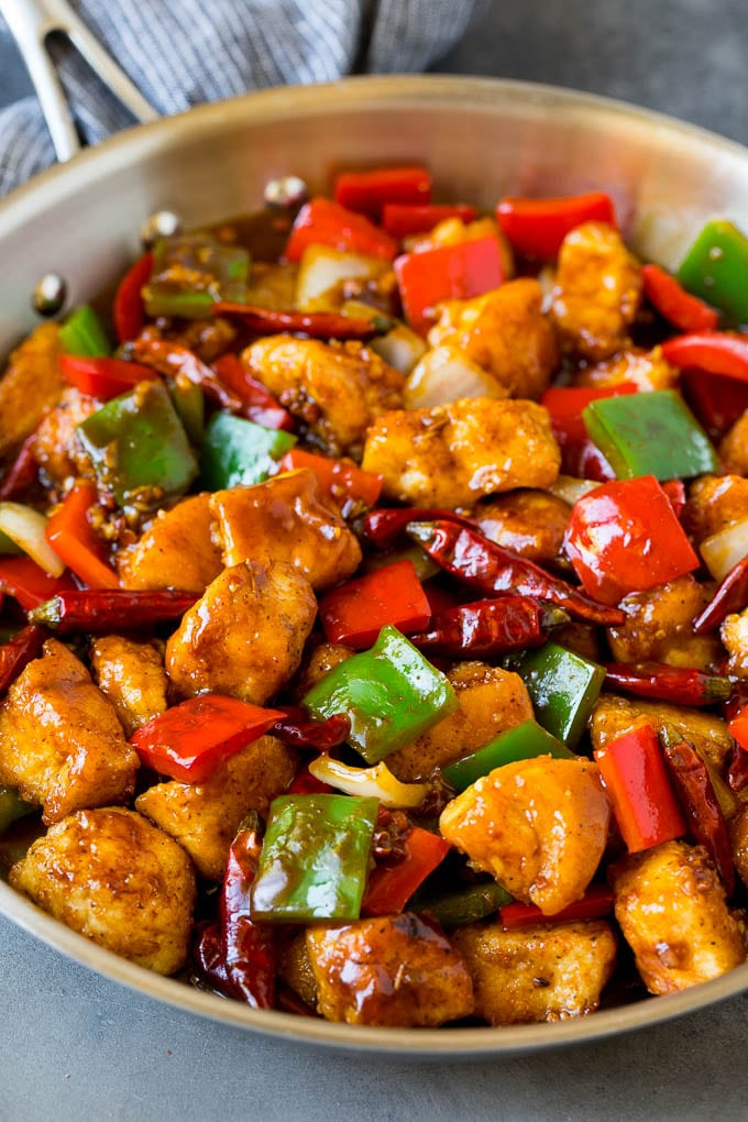 Szechuan chicken with vegetables and chili peppers in a skillet.