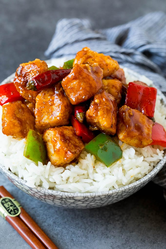 Szechuan chicken served over steamed rice in a bowl.