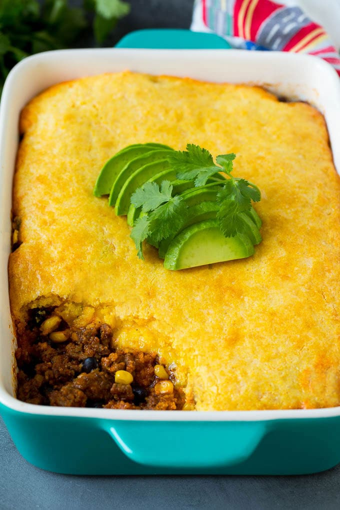 Tamale pie topped with sliced avocado and cilantro.
