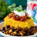 A slice of tamale pie topped with salsa and sour cream.