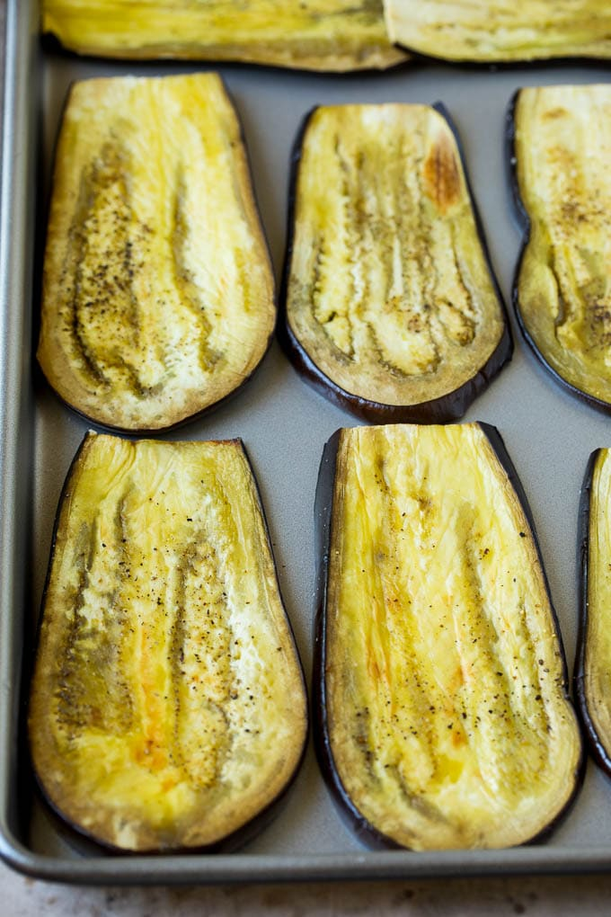 Roasted eggplant slices on a sheet pan.