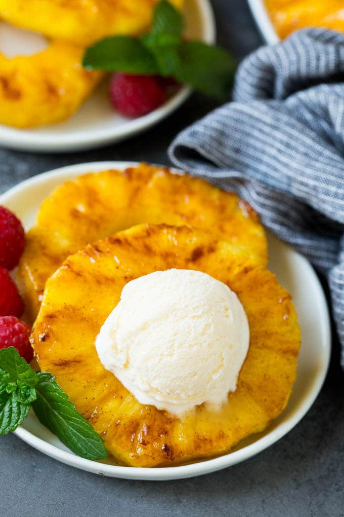 Grilled pineapple with a scoop of ice cream on top of it.