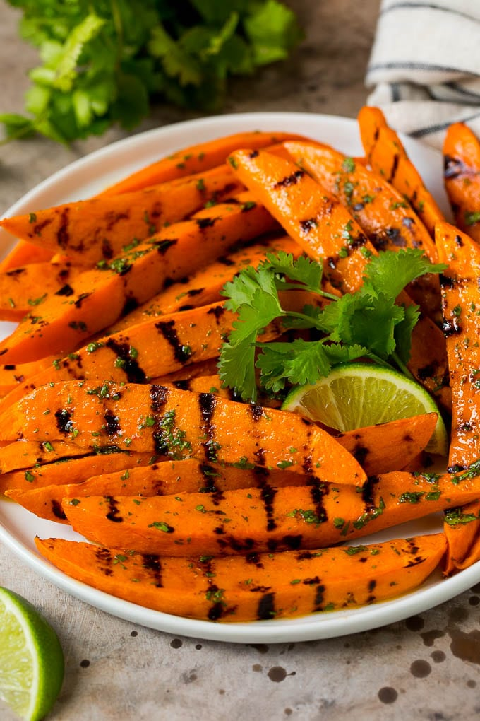 A plate of grilled sweet potatoes topped with lime dressing.