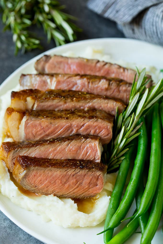 Sliced rib eye steak served with mashed potatoes and green beans.