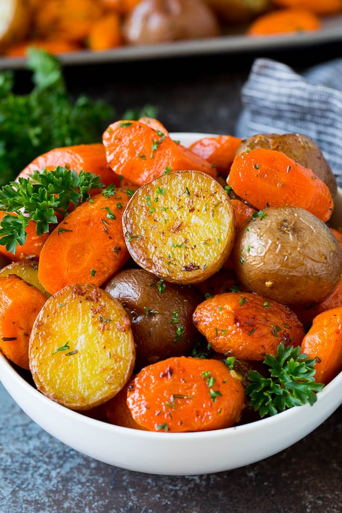 A bowl of roasted potatoes and carrots garnished with parsley.