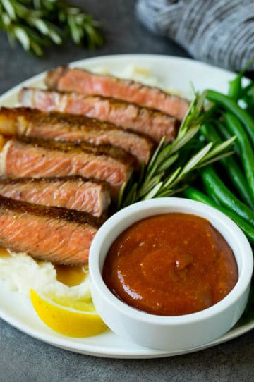 Homemade steak sauce served with sliced steak and green beans.