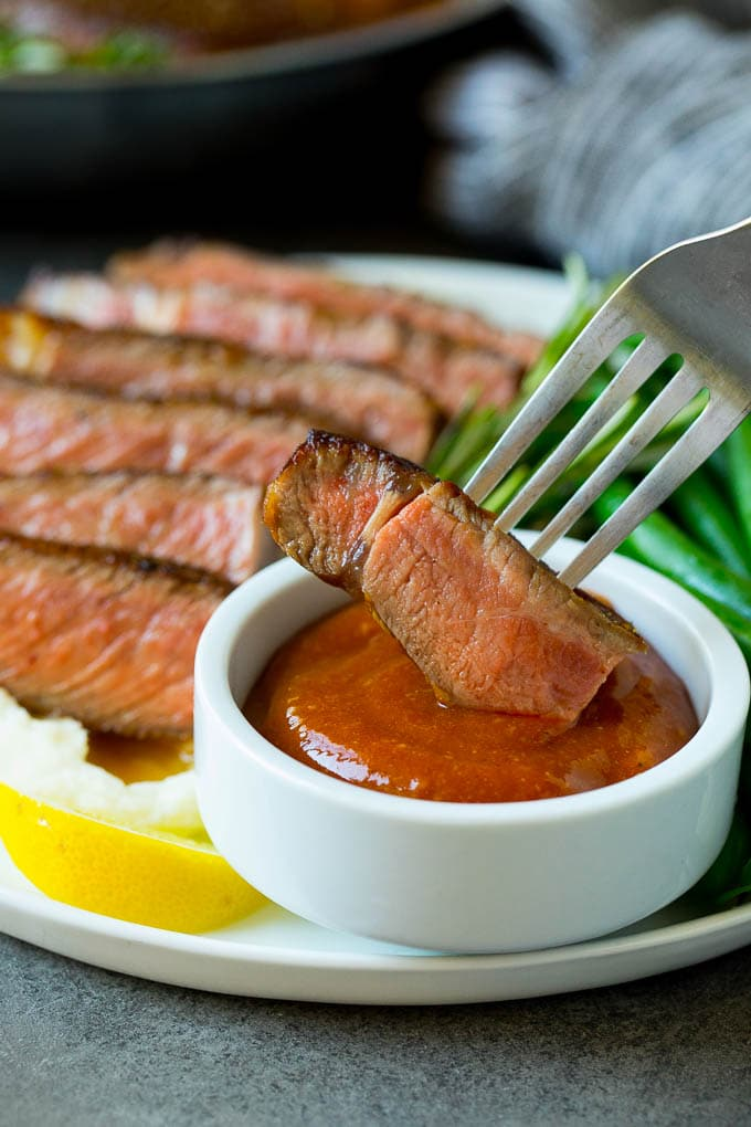 A fork dipping a piece of meat into steak sauce.