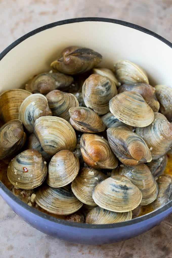 Littleneck clams in a pot with butter and white wine.