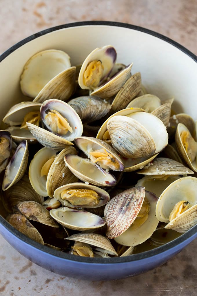 Cooked clams in a blue pot.