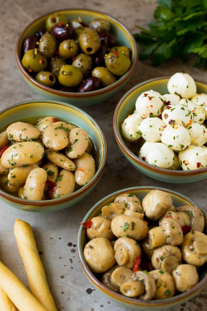 Bowls of mozzarella balls, marinated beans, mushrooms and olives.