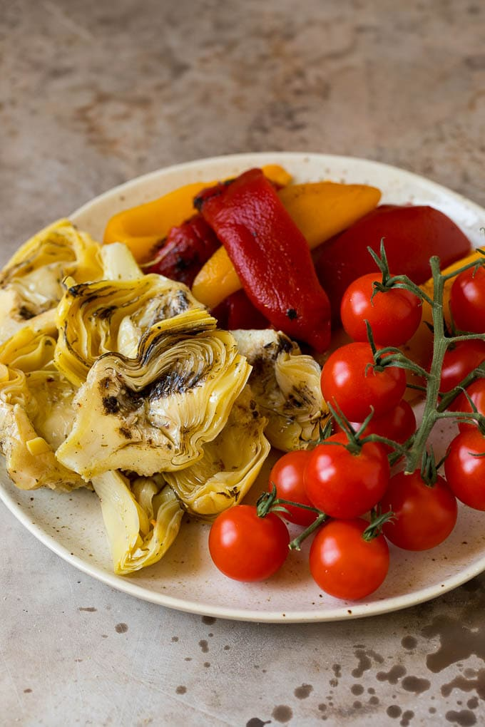 Roasted peppers, grilled artichokes and cherry tomatoes on a plate.
