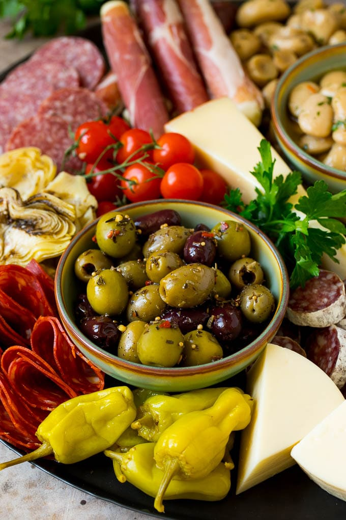 A close up of an antipasto platter with a bowl of olives, pickled vegetables, meats and cheeses.