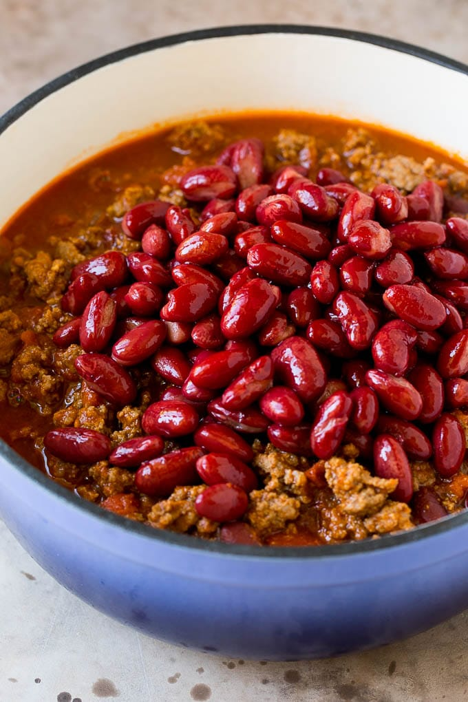 Kidney beans in a blue pot with a ground beef and tomato mixture.