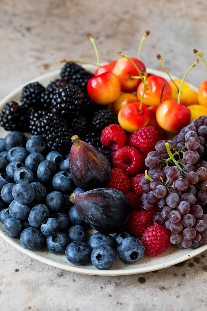 A plate of berries, cherries, grapes and figs.