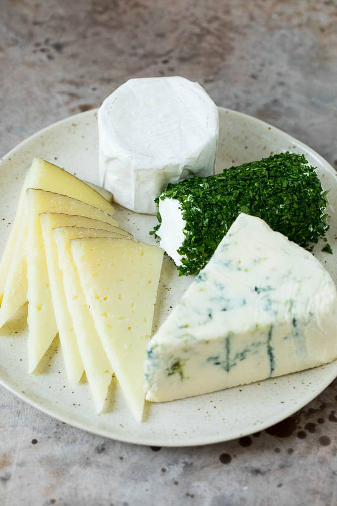 Four different types of cheese arranged on a plate.