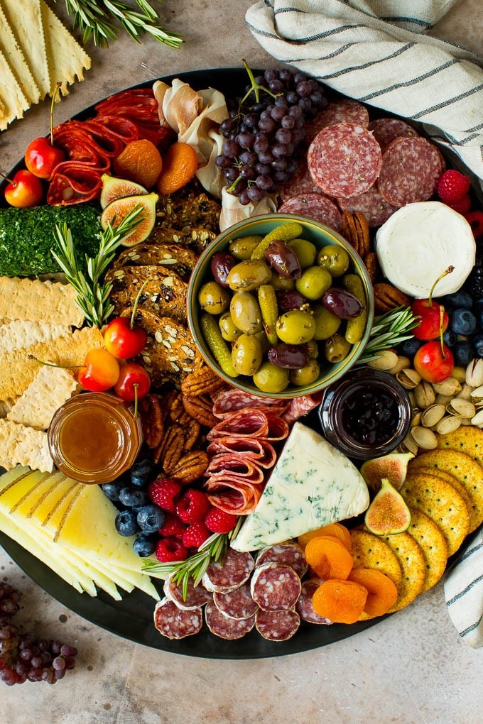 A charcuterie board filled with meats, cheeses, crackers, fruit and nuts.