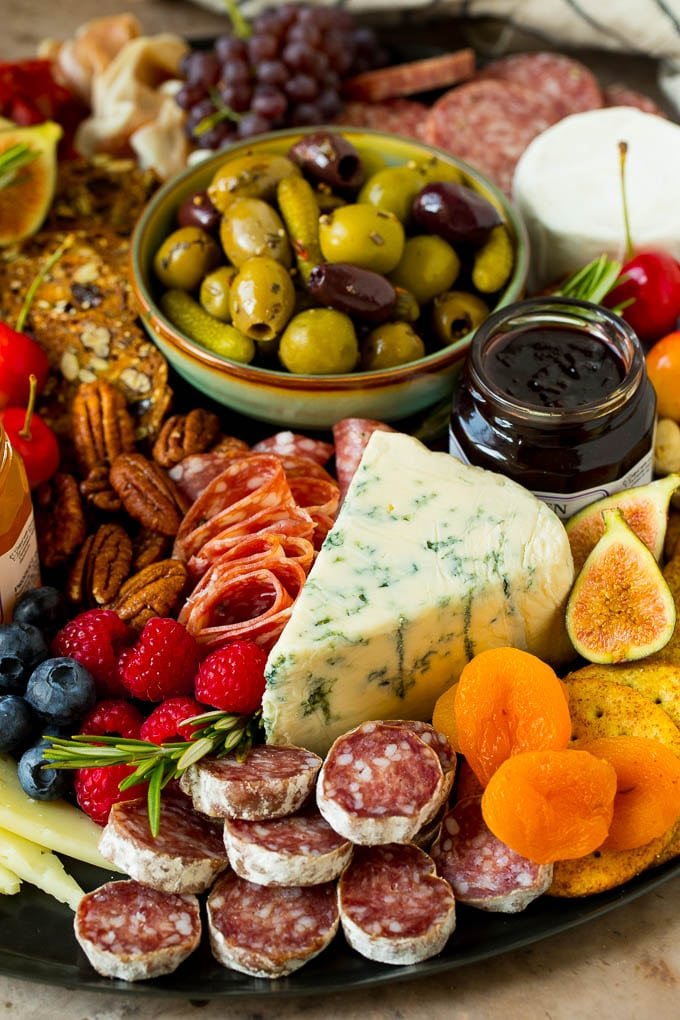 A charcuterie board close up with a wedge of cheese surrounded by salami, fruit and nuts.