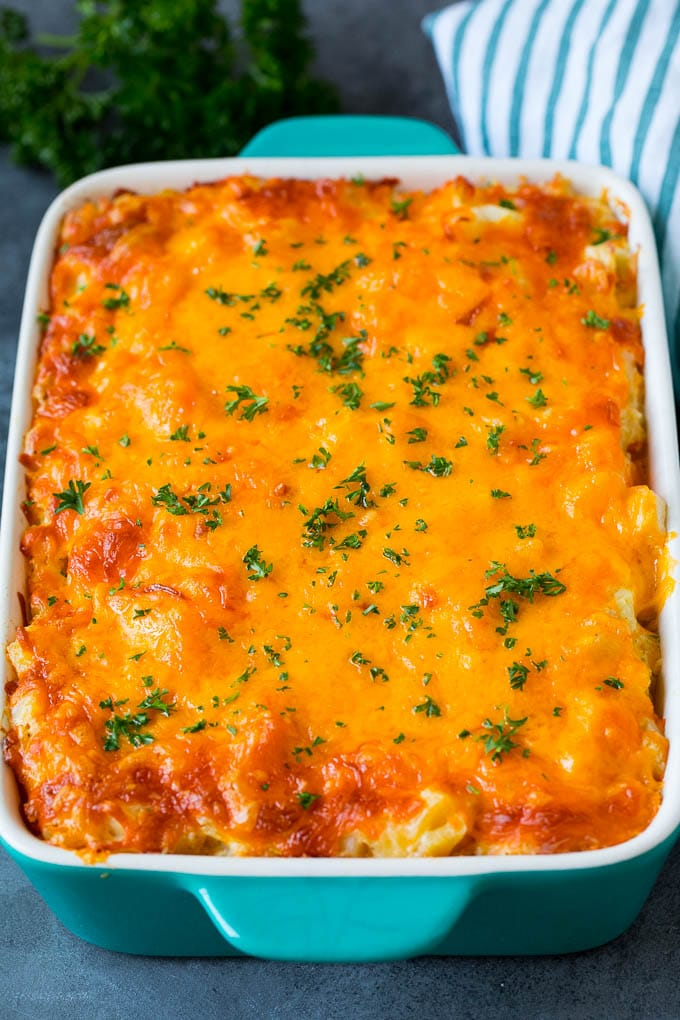 Cheesy potatoes in a casserole dish topped with melted cheddar and parsley.