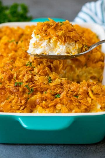A spoon serving up a portion of cheesy funeral potatoes.